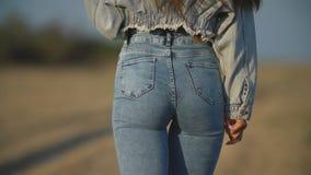Girl in jeans walks along the road