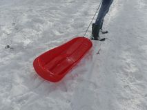 Girl in jeans and wellington boots pulling a red sledge in the snow royalty free stock images