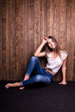 Girl in jeans and white shirt sitting down Stock Photography