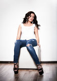 Girl in jeans and white singlet sitting on chair Stock Image