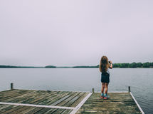 Girl on jetty taking picture