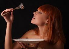 The girl with jewelry. The red-haired girl has control over a plug with a gold earring and a plate stock photo