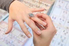 A girl in a jewelry store tries on her finger a gold ring with diamonds on the background of a shop window. Buying and shopping. A girl in a jewelry store tries stock photos