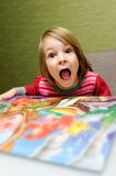 Girl with jigsaw puzzle. Cute young girl with open mouth and jigsaw puzzle in foreground royalty free stock photography