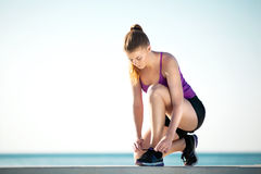 Girl jogger sitting and lacing up her running shoes. Young female runner is tying her running shoes on the ground Stock Image