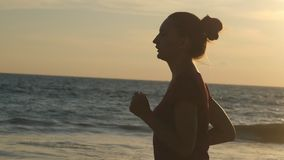 Girl jogging along ocean shore during sunrise. Silhouette of young woman running on sea beach at sunset. Female. Sportsman exercising outdoor. Healthy active stock video