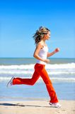 Girl jogging on the beach stock image