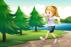 A girl jogging near the pine trees at the riverbank Royalty Free Stock Photo