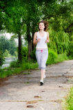 Girl jogging through a park. Girl  jogging along a path through a park as she takes her daily exercise to keep fit Stock Photography