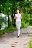 Girl jogging through a park Stock Photography