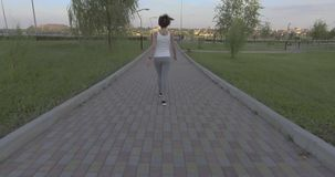 A girl while jogging in park. A girl while jogging in the park stock footage