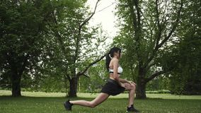 Girl jogging in the park. sportswoman doing stretching before jogging. Young woman doing sports in nature. Girl jogging in the park. Young woman doing sports in stock video footage