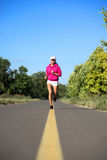 Girl jogging on road Royalty Free Stock Photos