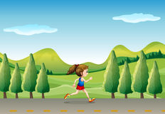 A girl jogging at the street with trees Stock Photo