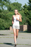 Girl jogging in summer park Royalty Free Stock Photo