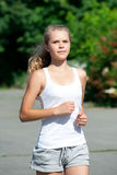 Girl jogging in summer park Royalty Free Stock Photos