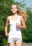 Girl jogging in summer park Stock Photos