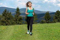 Girl jogging on trail in mountains on field with grass in summer sunny day. Stock Photos