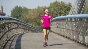 Girl Jogging via a pedestrian bridge in the city. Stock Photo