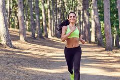 A girl jogging in the woods outdoors. Healthy lifestyle royalty free stock photos