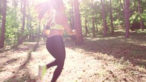 A girl jogging in the woods outdoors. stock video