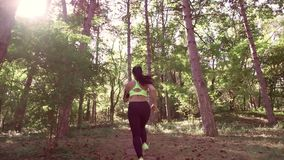 A girl jogging in the woods outdoors. stock footage