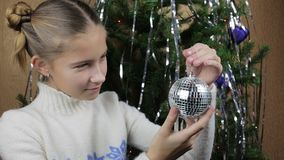 The girl joyfully looks at a mirror ball. Toy for a Christmas tree stock video footage