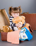 Girl joyfully sits in an old suitcase Royalty Free Stock Photos
