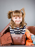 Girl joyfully sits in an old suitcase Stock Photo