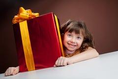 Girl joyously embraces the present Stock Photography