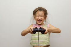 Girl with joystick. Excited little girl playing video game and smiling Royalty Free Stock Images