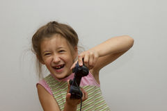 Girl with joystick. Excited little girl playing video game and smiling Stock Photo