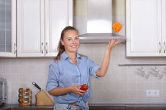 Girl juggles red bell pepper. In kitchen room Stock Images