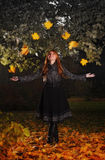 Girl juggling leaves in autumn park Royalty Free Stock Image