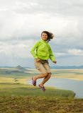 The girl in a jump. The girl jumps at top of mountain against a landscape royalty free stock photos