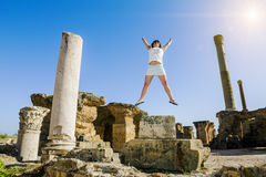 Girl in jump amid the ruins of Carthage in Tunisia Stock Photo