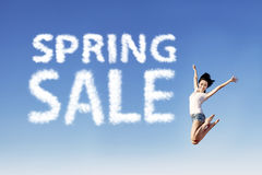 Girl jump announce spring sale. Young girl is jumping beside spring sale shape clouds under blue sky Stock Image