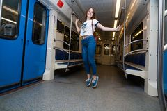 Girl jump in empty subway train. She is in blue jeans and white t-short royalty free stock photo