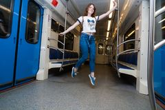 Girl jump in empty subway train. She is in blue jeans and white t-short royalty free stock photos