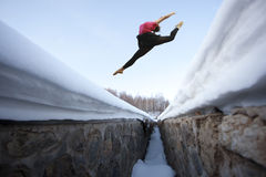 Girl jump high over snow mountain Stock Photography