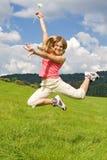 Girl jump on meadow Stock Photos