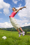 Girl jump on meadow Stock Photos