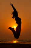 The girl in a jump and orange sunset Royalty Free Stock Photo