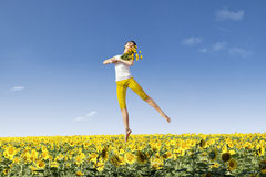 Girl jump over yellow flowers Royalty Free Stock Image