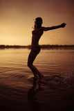 Girl jump in river at sunset Royalty Free Stock Image