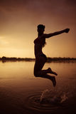 Girl jump in river at sunset Stock Photography