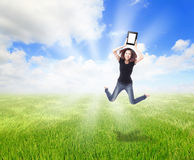 Girl Jump and show touch pad pc on the meadow Stock Photography