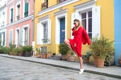 Girl jump on street of paris, france. Woman in sunglasses, in red dress, sneakers at house. Fashion, autumn style concept. Vacation, lifestyle, travelling Royalty Free Stock Image