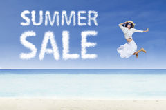 Girl jump and summer sale cloud. Girl jumping beside summer sale cloud on white sand Stock Image