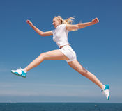 Girl is jumping. Vigorous blond woman in white sportwear is jumping outdoors Royalty Free Stock Image